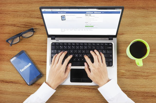 Hands opening facebook login page on laptop