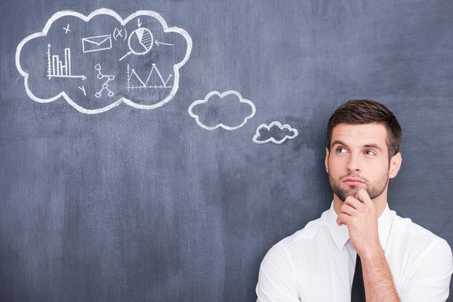 I need to think. Picture of handsome young man holding hand on chin and thinking while standing against cloud chalk drawing on blackboard