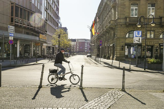 Old Man Riding Bicycle on Empty Street in Frankfurt During Lockdown
